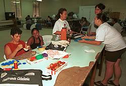 Dejanira (em pé ao fundo) dá aulas gratuitas de corte e costura para seus alunos na Vila São Pedro