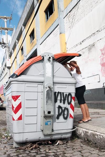 Moradora coloca o lixo doméstico em container da coleta automatizada.