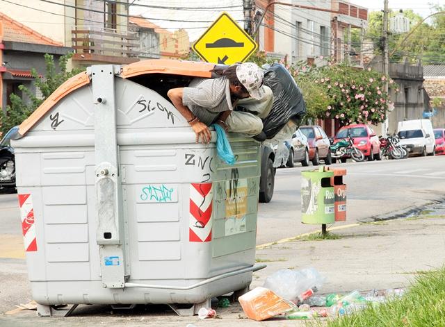 Catador procura alimento dentro de container de lixo orgânico.
