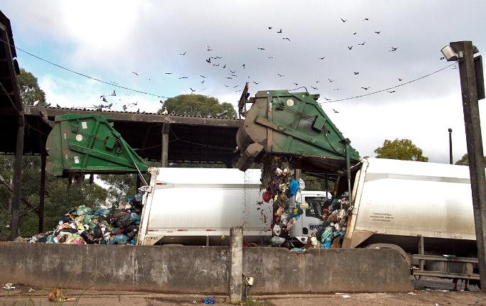 Momento em que caminhões descarregam os resíduos diversos