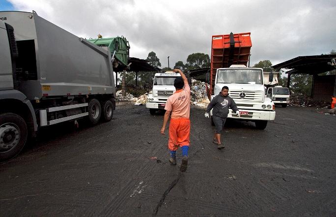 Funcionários controlam a posição dos caminhões no terreno