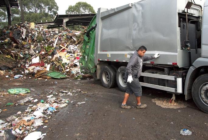 Caminhão com resíduos orgânicos de estabelecimento comercial libera líquido produzido durante o transporte, enquanto funcionário observa