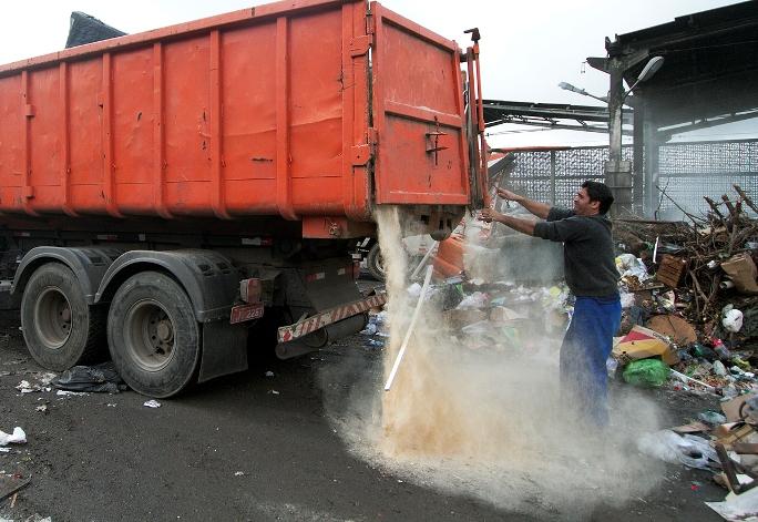 Sem nenhum equipamento de proteção individual (EPI), funcionário descarrega caminhão