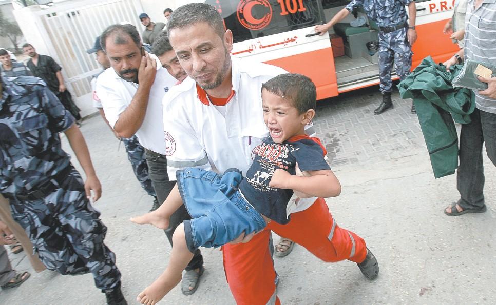 Paramédico carrega uma criança ferida para o hospital após um ataque aéreo israelense, na cidade de Rafah, ao sul da Faixa de Gaza