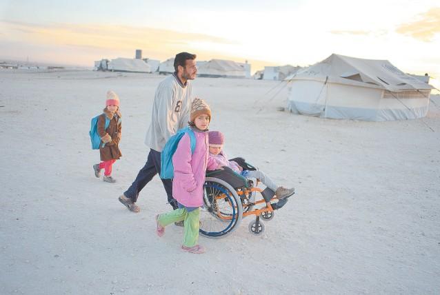 Refugiado sírio em acampamento da ONU, na Jordânia, leva as três filhas para escola da Unesco na fronteira