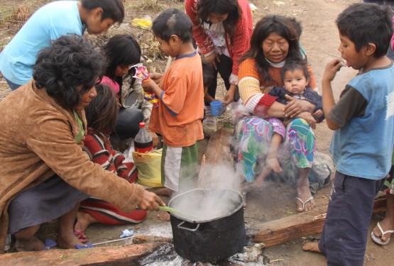 Em um dia frio de inverno deste ano, os índios se reúnem em volta do fogo em que cozinham uma carne de porco. Enquanto esperam a comida ficar pronta, uma cuia de chimarrão passa de mão em mão, o k'ãã, a bebida tradicional indígena, como mostra Karaí, um Mbya nascido em aldeia paraguaia e que mora no acampamento da BR-290. | Foto: Cristina Ávila