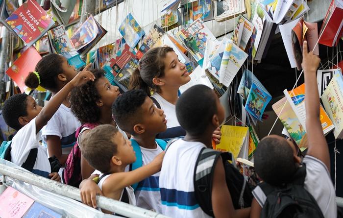 Crianças da comunidade escolhem livros na abertura da Festa Literária das Periferias (Flupp), no Rio de Janeiro