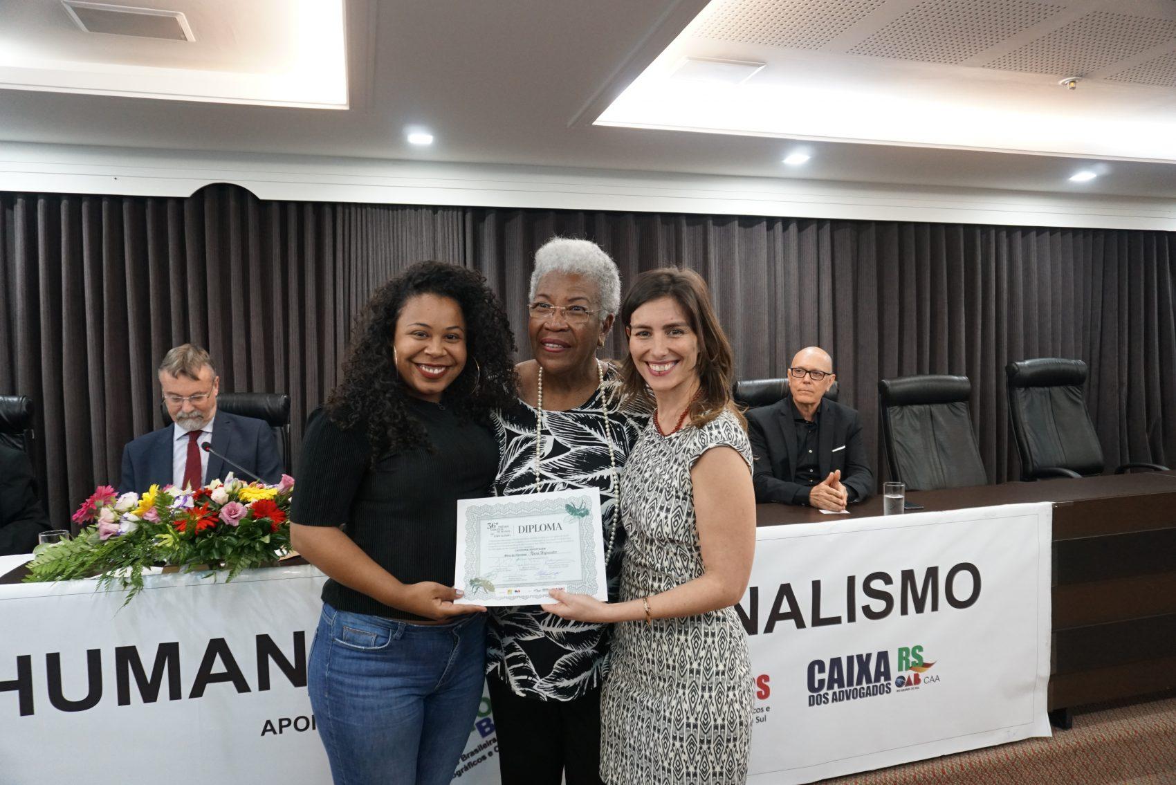Naira Hofmeister e Thayse Uchôa receberam o prêmio das mãos de Vera Deisy Barcellos, presidente de Sindicato dos Jornalistas