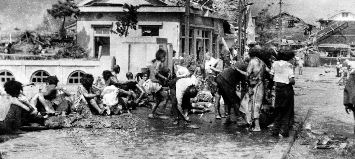 Civis feridos que escaparam a onda de calor, reuniram-se em uma calçada a oeste de Miyuki-bashi em Hiroshima, Japão, por volta das 11 horas da manhã de 6 de agosto, de 1945