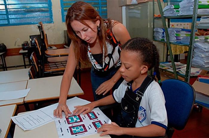 Criança com deficiência visual recebe atenção de professora em escola de Goiás: legislação internacional e nacional determina que pessoas com deficiência devem ser incluídas em escolas comuns