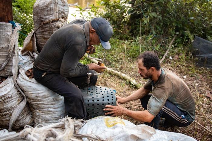 Braz e o sobrinho Maciel constroem equipamento para aproveitar a água do Jari e lavar a castanha, antes de embarca-la na canoa