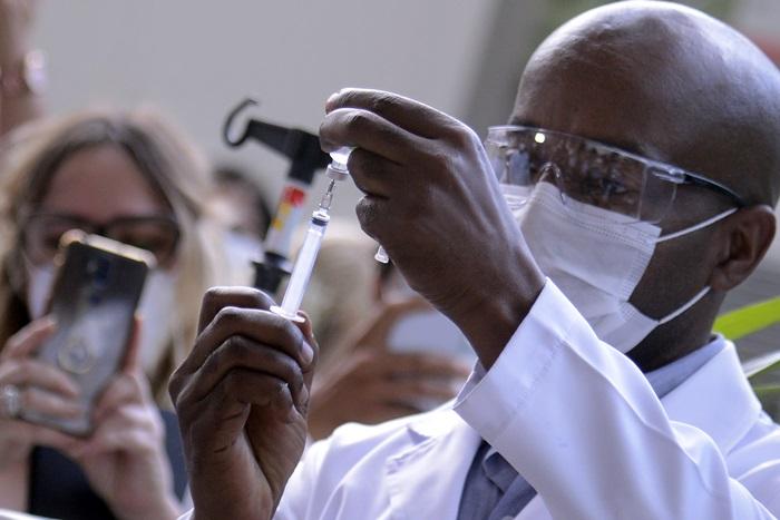 Servidor da Fiocruz prepara vacina de Oxford/AstraZeneca para a primeira aplicação no Brasil