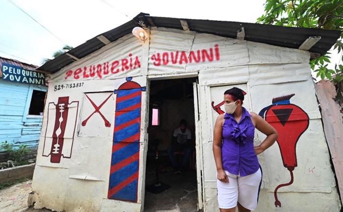 """Com o confinamento, a cabelereira Julissa Álvarez, 44 anos, da República Dominicana perdeu seus clientes e o ofício com o qual colocava comida na mesa dos seis filhos e o companheiro. Agora ela recebe apoio e vale-alimentação do projeto """"Closing Gaps"""" apoiado pela Oxfam e outras organizações"""