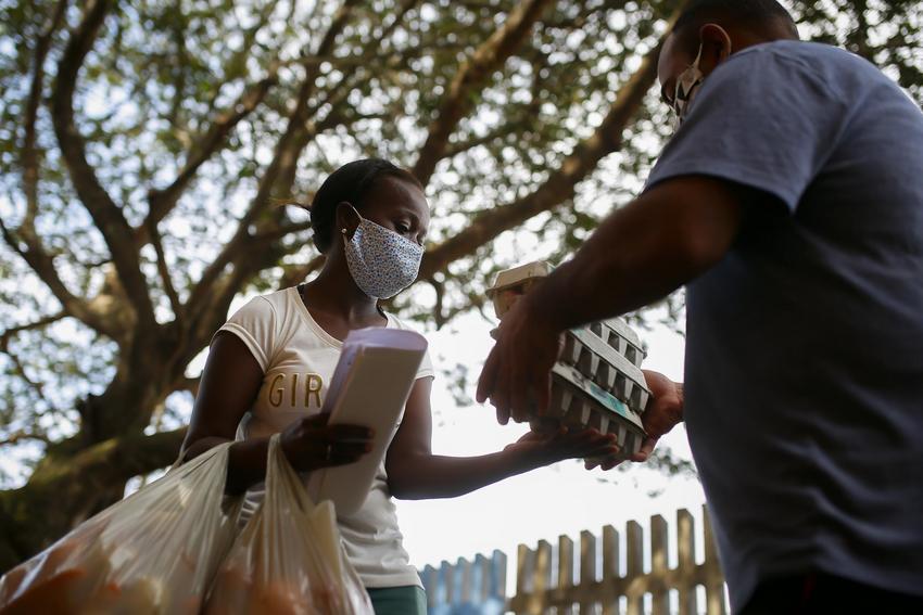 Estudante da rede municipal recebendo cesta básica durante ação da SMED