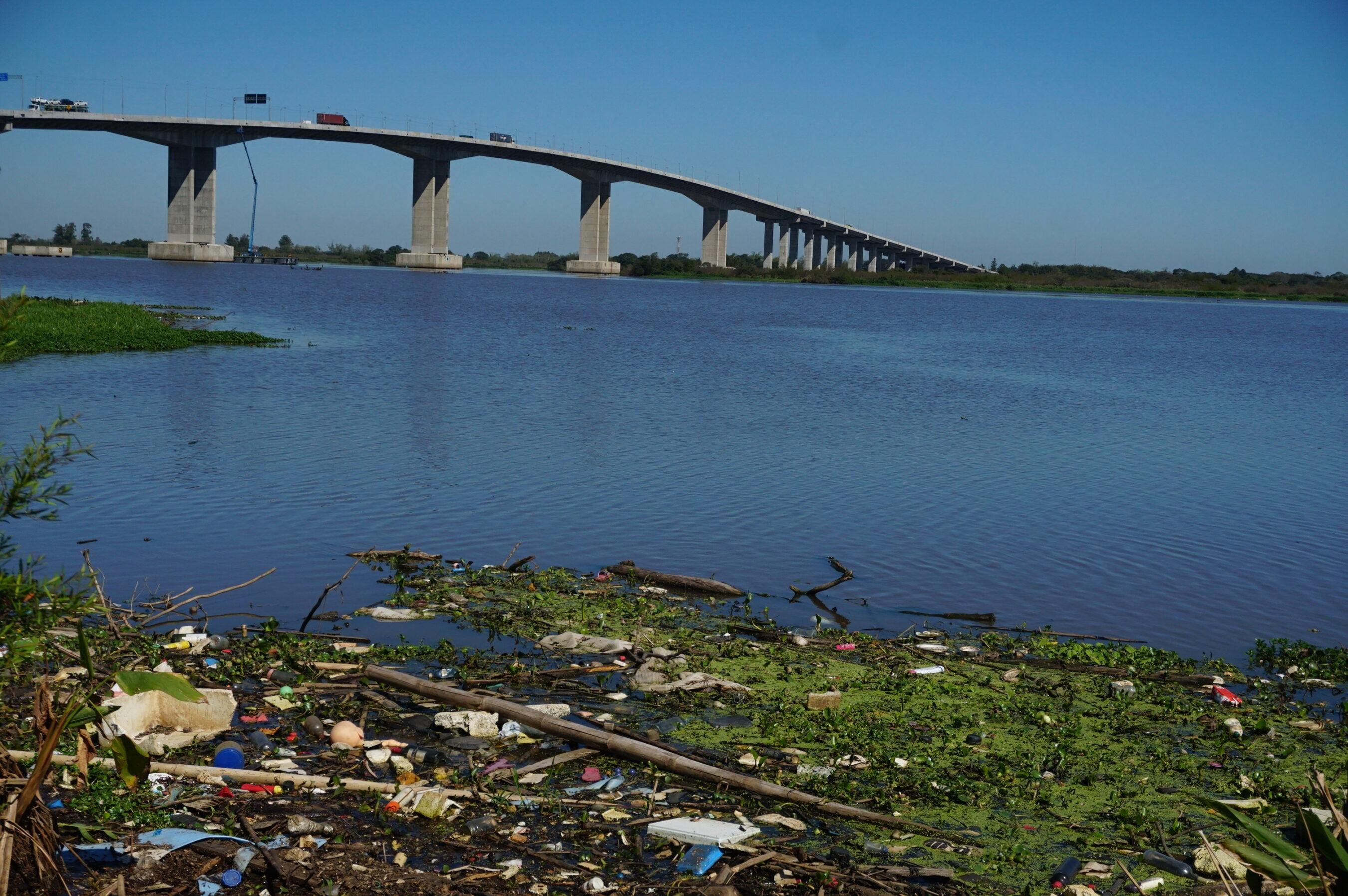 Resíduos sólidos acumulados na margem do Guaíba, perto da entrada de acesso à Capital