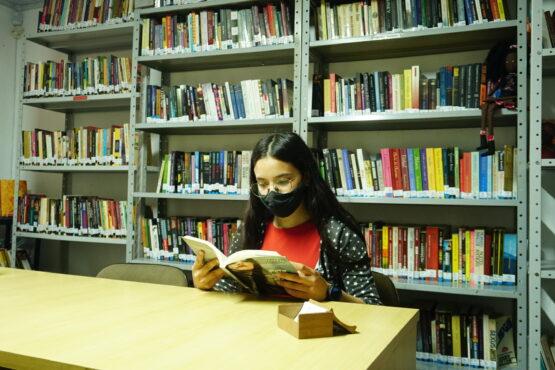 Máscara no rosto livro nas mãos | Foto: Igor Sperotto
